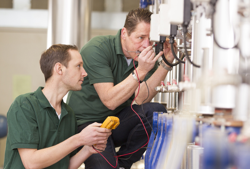 Senior technician and junior technician repairing agriculture machinery in a greenhouse