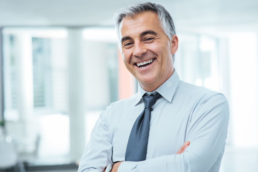 Successful businessman posing with crossed arms and smiling at camera