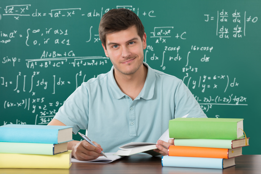 Young Happy Man Writing In Book With Pen At Desk